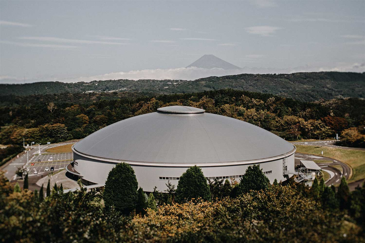 Exterior view of Izu Velodrome sitting amongst the forest and Mount Fuji in Japan