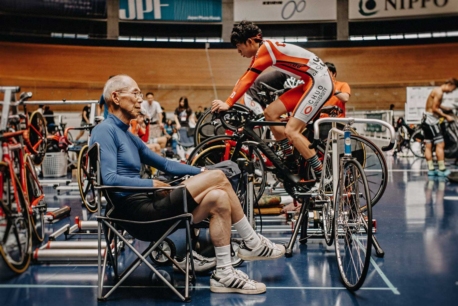 Older cyclist sits beside young track cyclist at the National Track cycling championships at Izu Velodrome, Japan