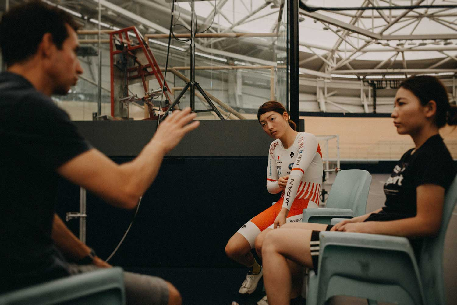 Japanese track cyclist discuss performance with Biomechanist during training session at velodrome