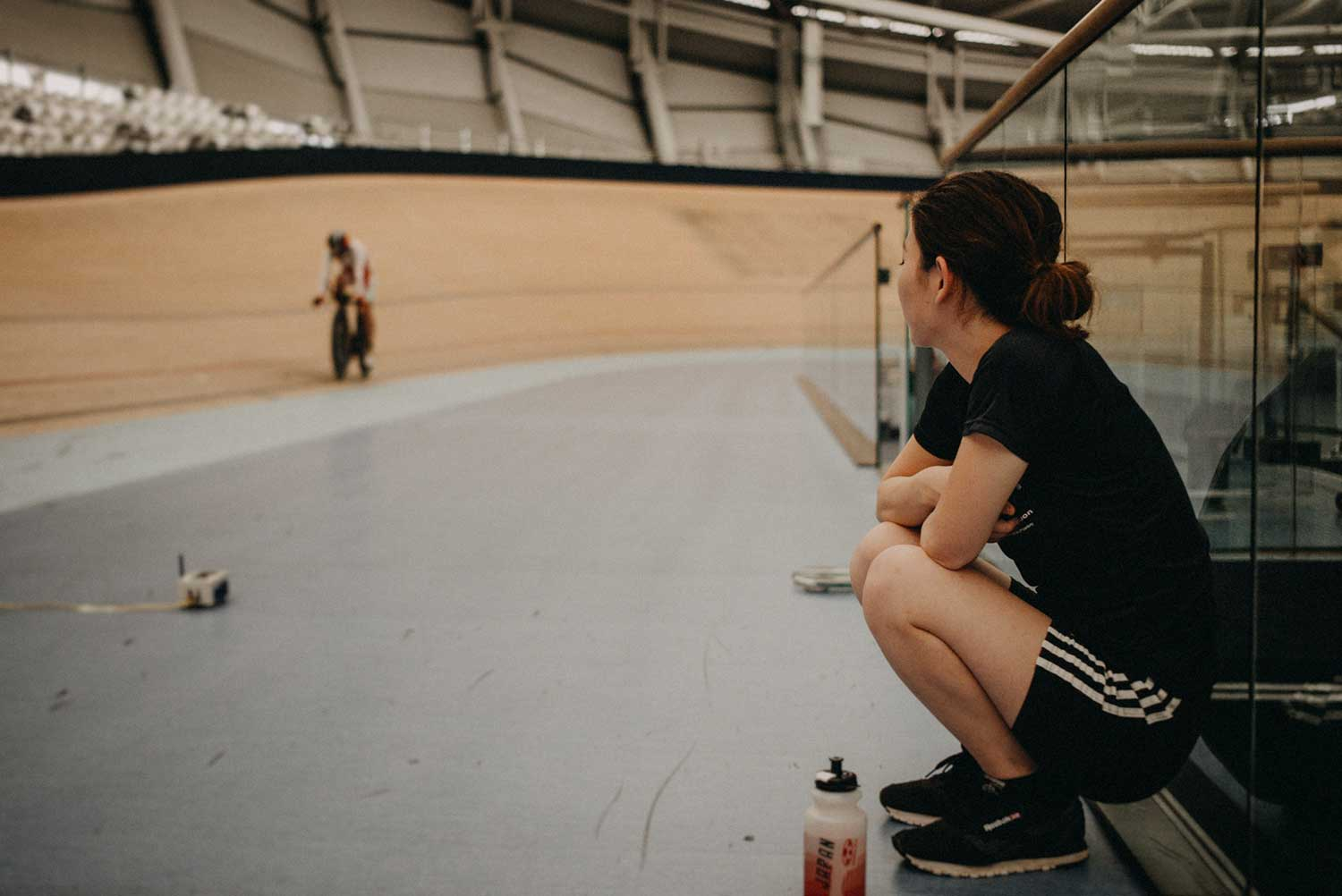 Cycling Physiotherapist watches cyclist training on the velodrome