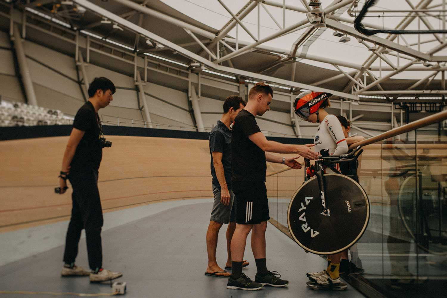 Cycling biomechanists weight track cyclist with bike at the velodrome during training session