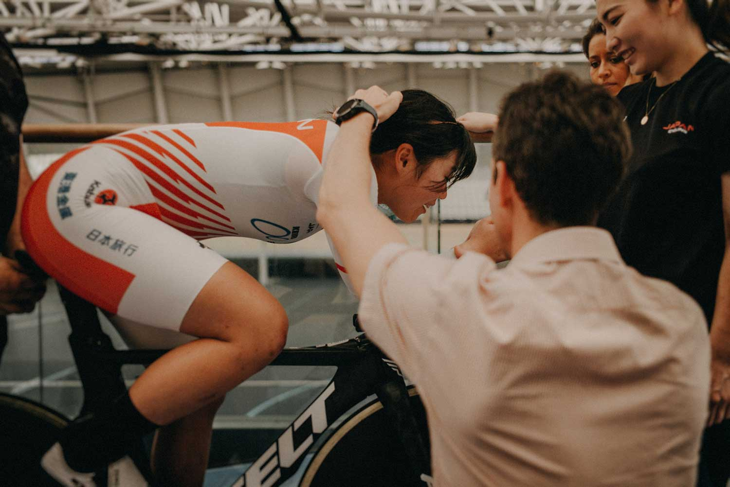 Cycling biomechanist adjusts body position of Japanese track cyclist during training session at velodrome