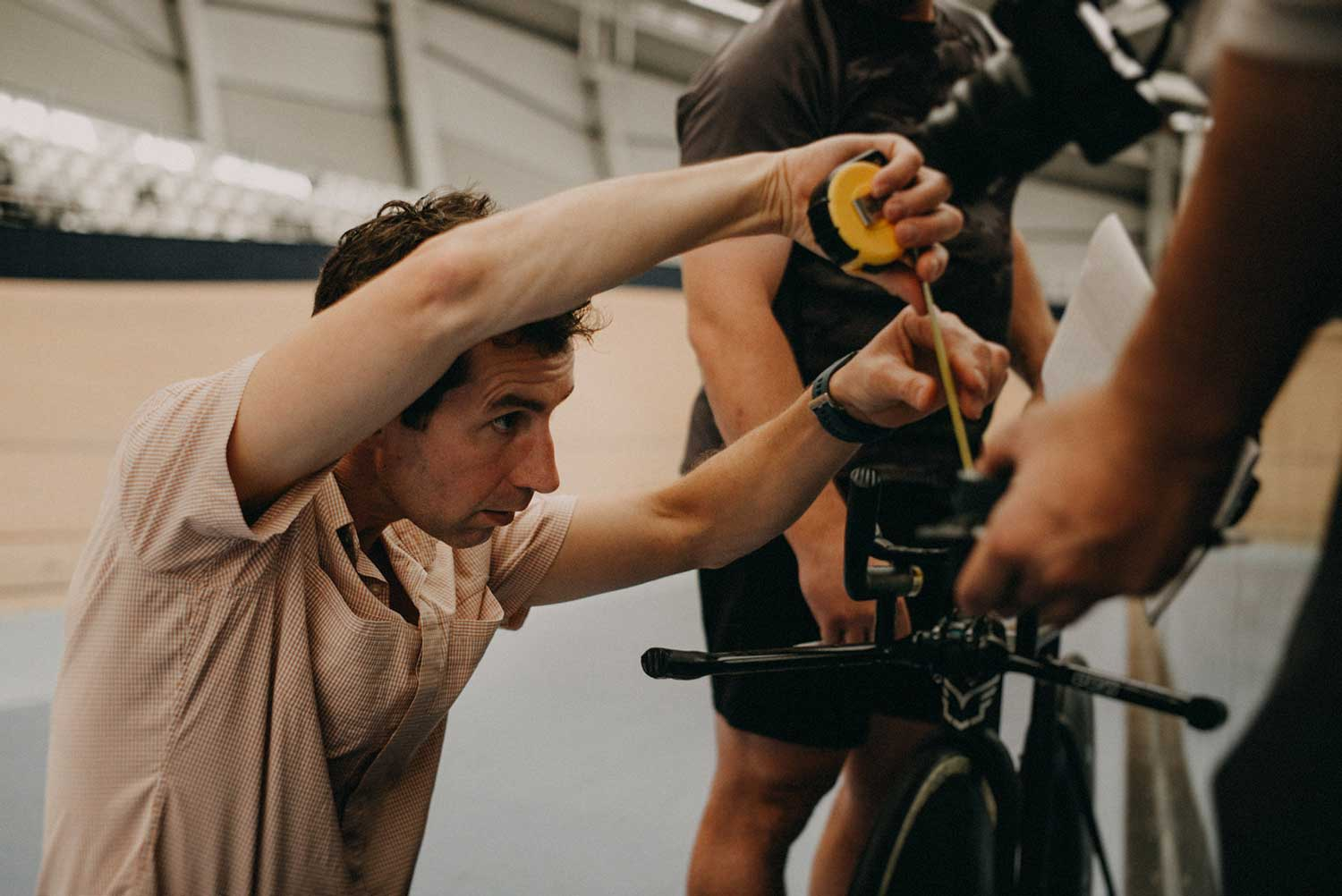 Cycling biomechanist checks bike fit for accuracy during rtaining session at velodrome