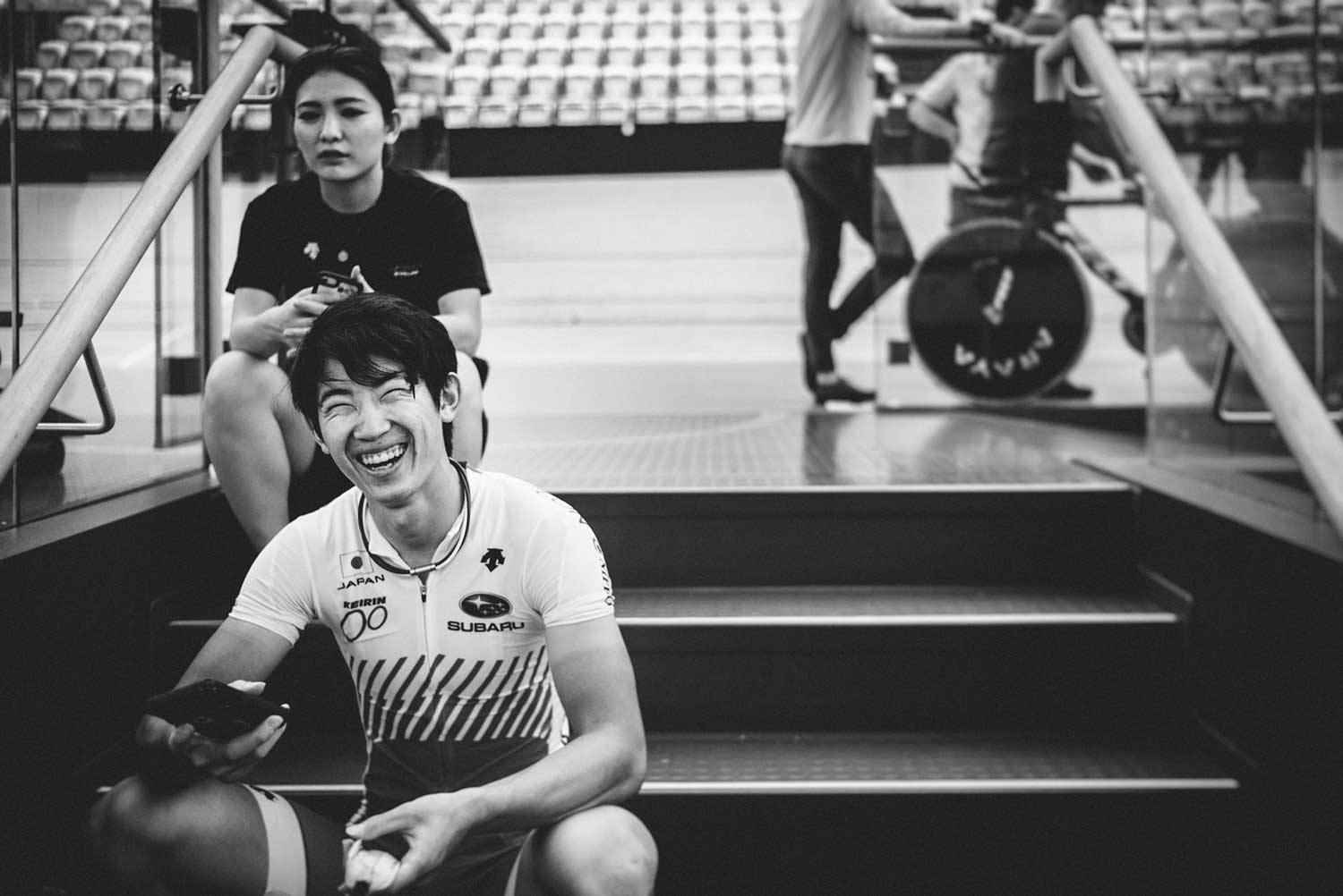 Japanese track cyclist laughs whilst having a break at velodrome during trainin session