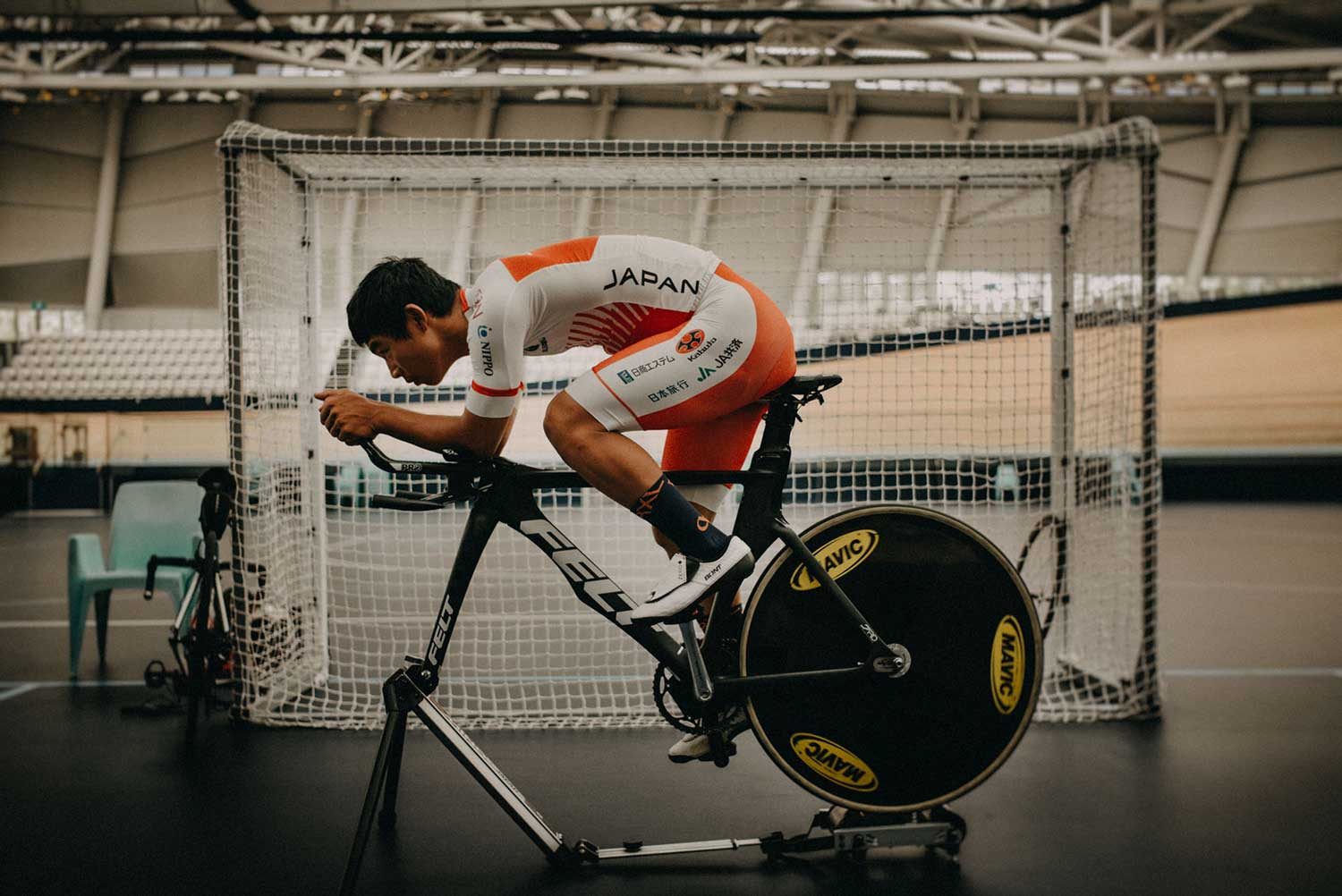 Japanese track cyclist trains on static bike with aerobars at velodrome during training session