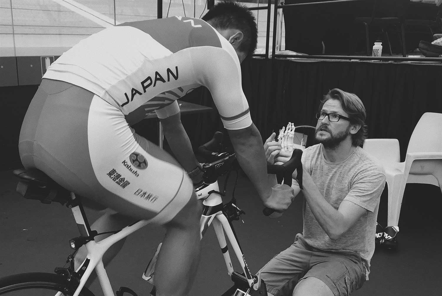 Japanese track cyclist talks to podiatrist when fitting foot orthotics at velodrome during training session