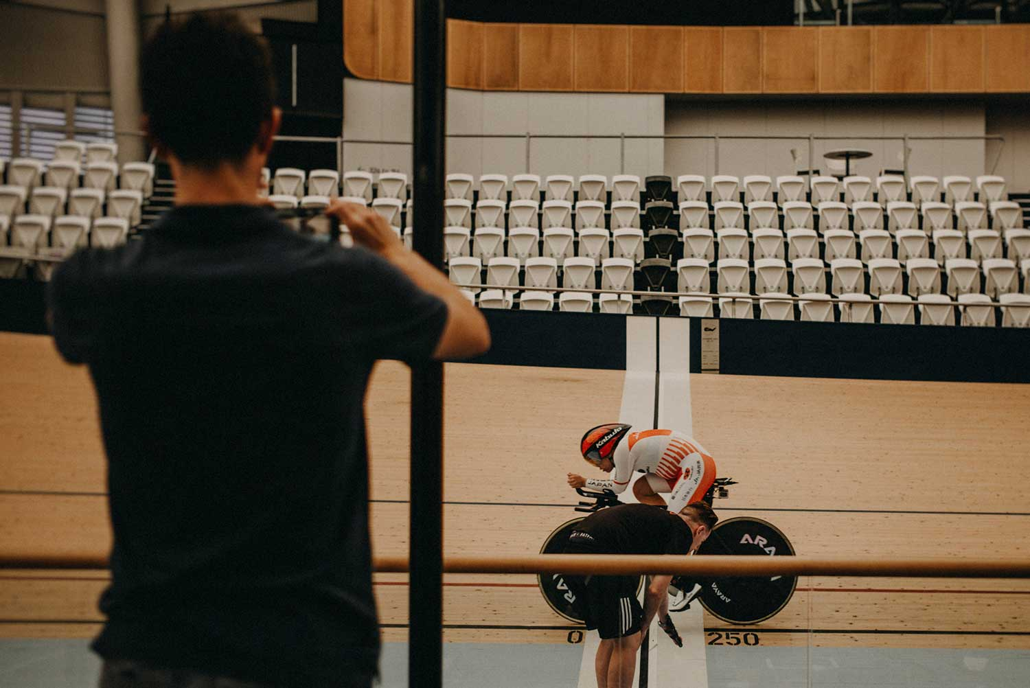 Japanese cyclist crosses finish line whilst training at velodrome for time trial with coaches watching