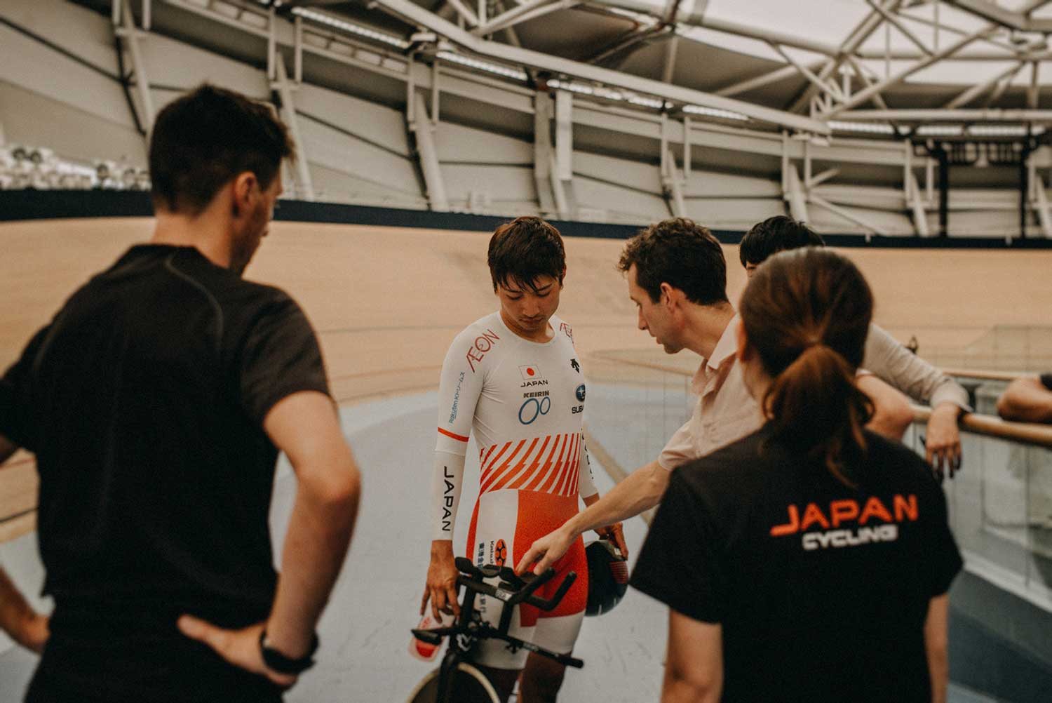 Japanese cyclist discusses performance with coaches after training in velodrome