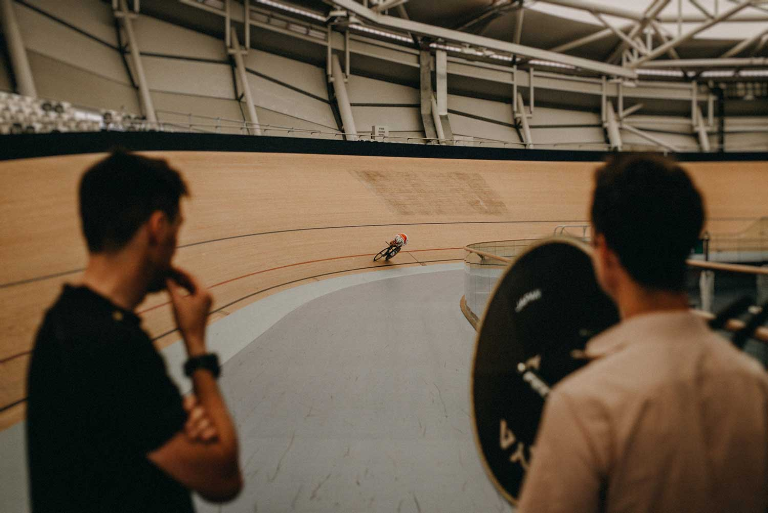 Japanese cyclist training for individual time trail in velodrome with coaches watching