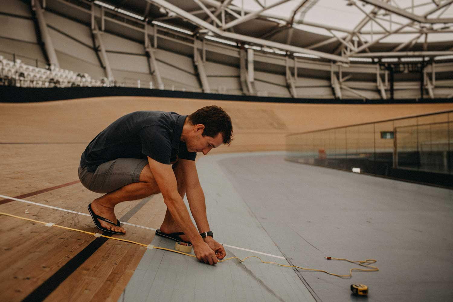 Team Japan Cycling Biomechanist prepares track for testing during cycling training session at velodrome